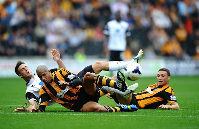 HULL, ENGLAND - AUGUST 24: Ricky Van Wolfswinkel of Norwich City battles with James Chester and Curtis Davies of Hull City during the Barclays Premier League match between Hull City and Norwich City at KC Stadium on August 24, 2013 in Hull, England. (Photo by Laurence Griffiths/Getty Images)