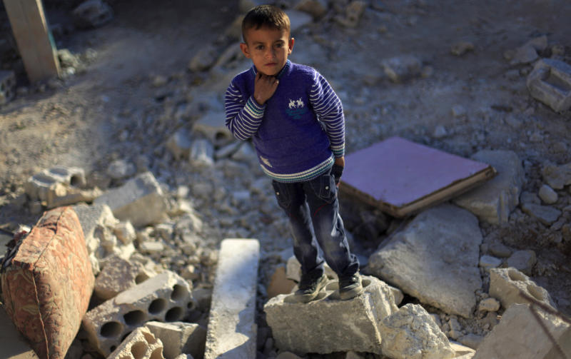 A Syrian boy stands on the rubble of a house that was destroyed by an airstrike last Tuesday killing several Syrians in the Maret El-Nasaneh village on the outskirts of Idlib, Wednesday, Nov. 14, 2012. (AP Photo/ Khalil Hamra)
