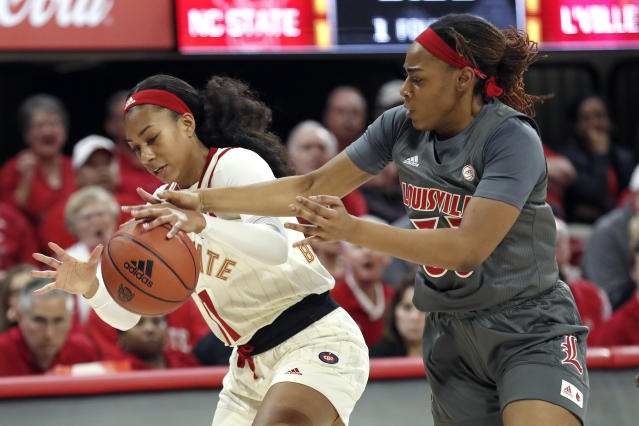 North Carolina State guard Jakia Brown-Turner, left, and Louisville forward Bionca Dunham reach for the ball during the first half of an NCAA college basketball game in Raleigh, N.C., Thursday, Feb. 13, 2020. (AP Photo/Gerry Broome)