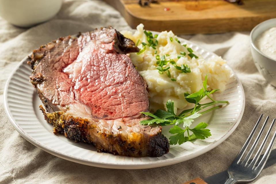 <p>The confusion around prime rib starts with its definition. Also known as beef rib roast and standing rib roast, prime rib refers to the rib section of the cow that has been cut between the fifth and 12th ribs. If you cut a steak from between the rib bones, then you've got a rib-eye steak (New York strip and Delmonico cuts also come from this part of town). If you keep it all together, then it's a roast. The name standing rib roast comes from the fact that it is traditionally cooked standing on the rib bones. Prime rib has it all going on; it's the most tender cut of beef after the nearby tenderloin, but because it has more marbling (aka fat), it is way more flavorful than its lean cousin.</p>