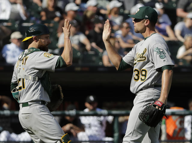 Oakland Athletics relief pitcher Blake Treinen, right, celebrates with catcher Jonathan Lucroy after they defeated the Chicago White Sox in a baseball game Saturday, June 23, 2018, in Chicago. (AP Photo/Nam Y. Huh)