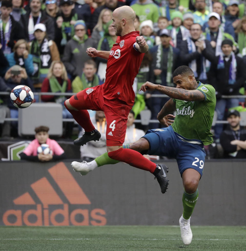 Toronto FC's Michael Bradley, left, and Seattle Sounders' Roman Torres battle for the ball Sunday, Nov. 10, 2019, during the first half of the MLS Cup championship soccer match in Seattle. (AP Photo/Elaine Thompson)