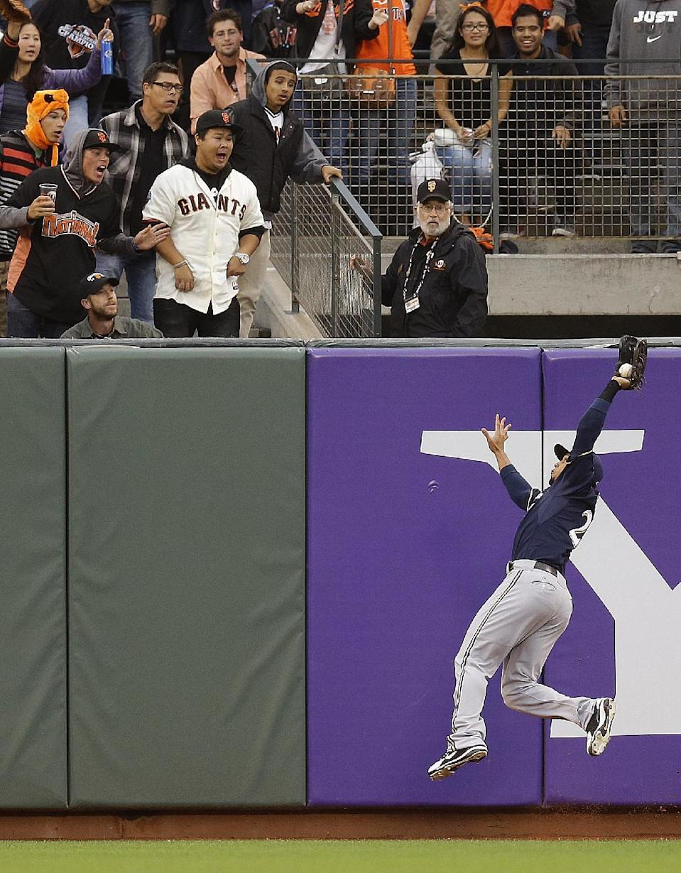 Milwaukee Brewers' Carlos Gomez catches a ball hit by San Francisco Giants' Buster Posey in the first inning of a baseball game on Wednesday, Aug. 7, 2013, in San Francisco. (AP Photo/Ben Margot)