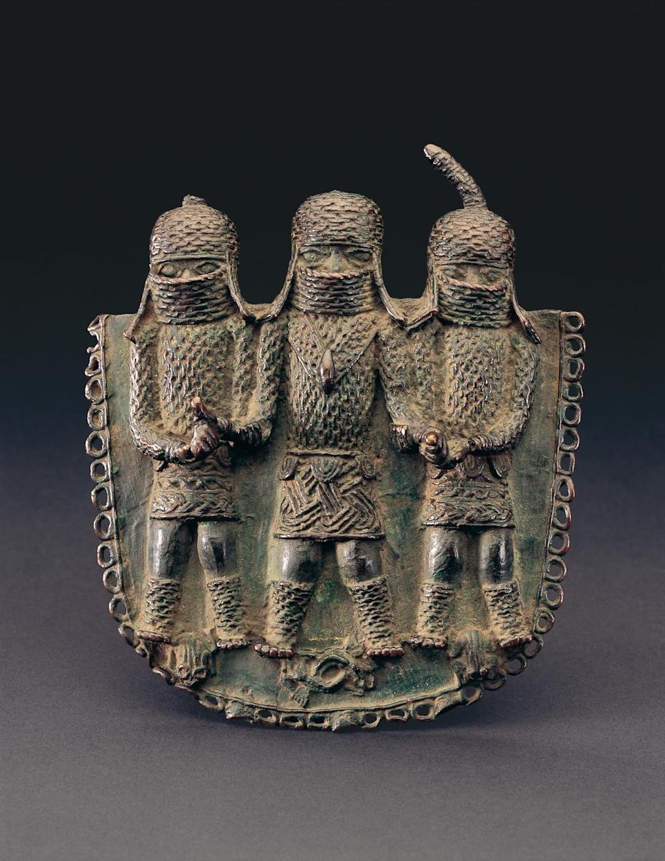A cast copper alloy Benin pendant with figures of three people in relief