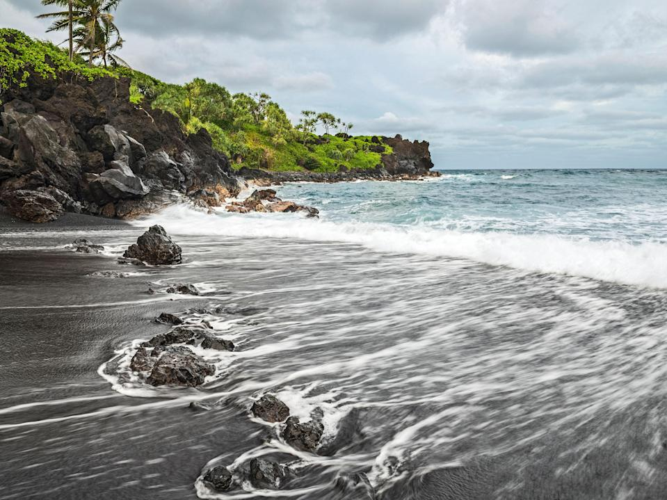 """With its jet-black shore, aquamarine waters, and jungle-like foliage, Hana's Honokalani Beach is one of Maui's most Instagram-worthy spots. But it's more than just a pretty face: beyond luxuriating on its onyx sand (actually millions of tiny lava pebbles), there's lots to do, from boogie-boarding to exploring the many sea caves carved into the cliffs along the shore. It's wild, unspoiled Hawaii at its best, and a necessary stop along the <a href=""""https://www.cntraveler.com/activities/maui/road-to-hana?mbid=synd_yahoo_rss"""" rel=""""nofollow noopener"""" target=""""_blank"""" data-ylk=""""slk:Hana Highway"""" class=""""link rapid-noclick-resp"""">Hana Highway</a>—just look out for mile marker 32."""
