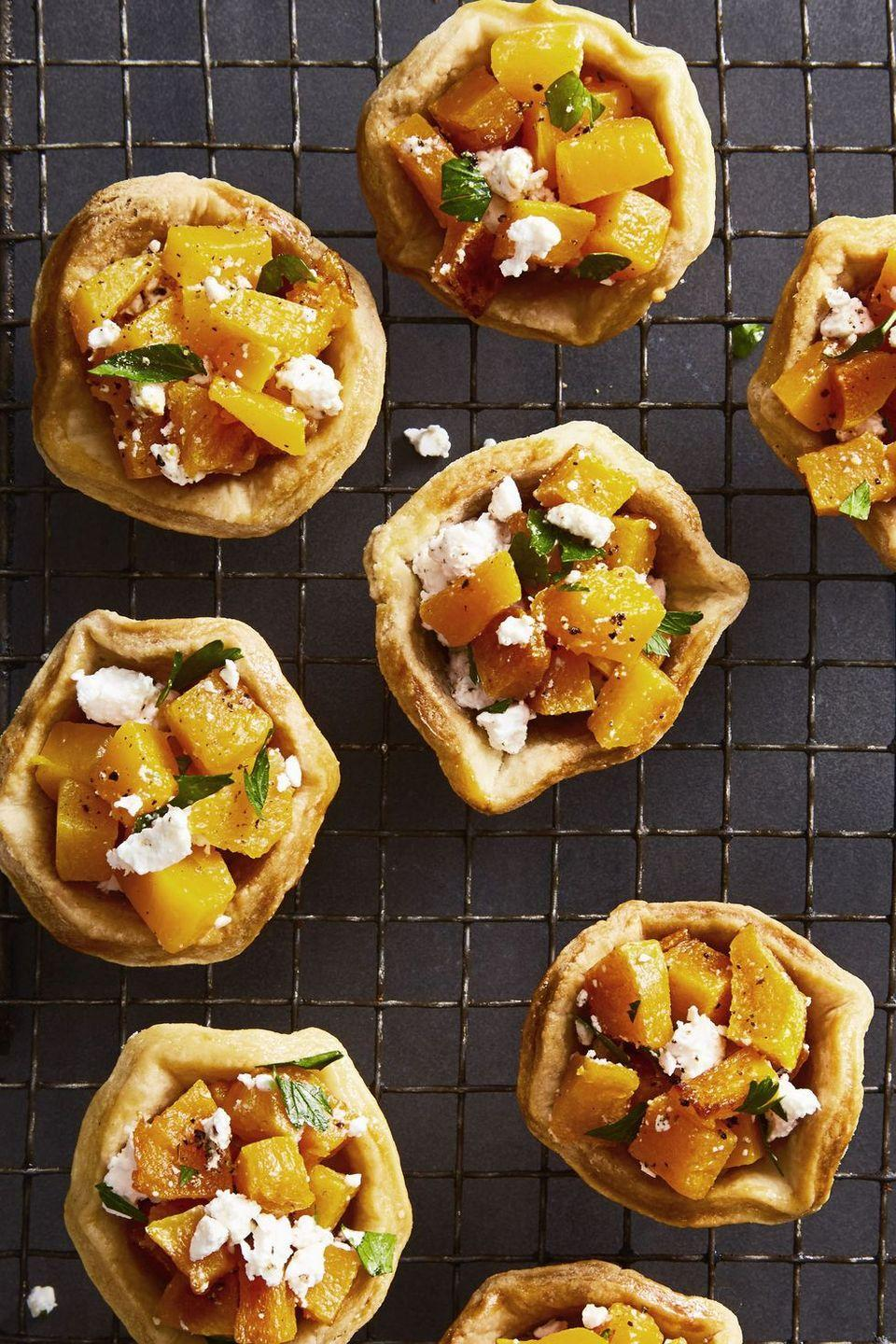 """<p>These little two-bite tartlets will feel especially personal and cute on a plate that's heaping with other sides. </p><p><strong><em>Get the recipe at <a href=""""https://www.goodhousekeeping.com/food-recipes/a46642/butternut-squash-and-feta-tartlets-recipe/"""" rel=""""nofollow noopener"""" target=""""_blank"""" data-ylk=""""slk:Good Housekeeping"""" class=""""link rapid-noclick-resp"""">Good Housekeeping</a>. </em></strong><br></p>"""