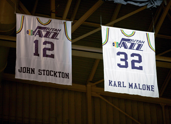 Former Utah Jazz forward Karl Malone's #32 jersey is retired to the rafters of the Delta Center next to long-time team mate John Stockton's #12 jersey during halftime of a Utah Jazz and Washington Wizards NBA basketball game in Salt Lake City March 23, 2006.  REUTERS/Steve Wilson