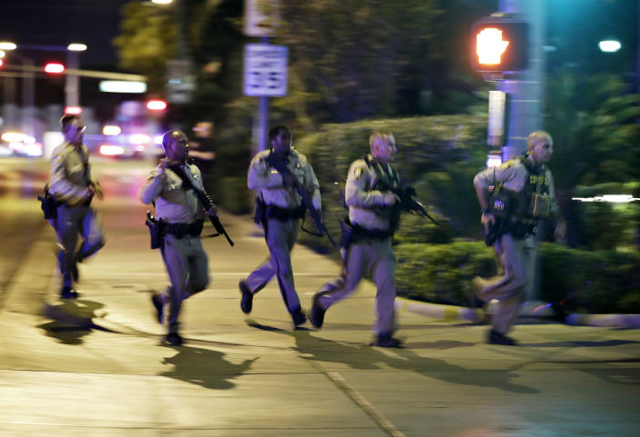 Police run to cover at the scene of the shooting on Oct. 1. (Photo: John Locher/AP)