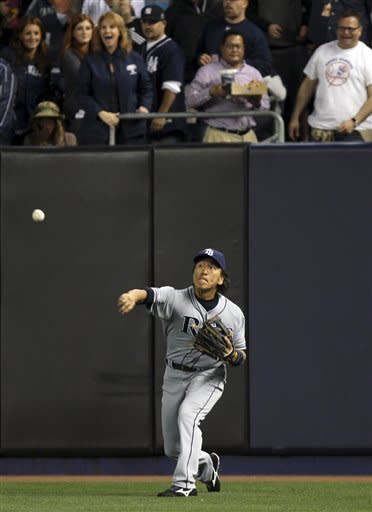 Tampa Bay Rays outfielder Hideki Matsui relays the ball after fielding a double hit by New York Yankees' Nick Swisher during the fifth inning of a baseball game at Yankee Stadium in New York, Tuesday, June 5, 2012. (AP Photo/Seth Wenig)