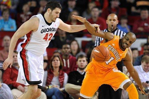 Georgia forward Nemanja Djurisic (42) and Tennessee guard Trae Golden (11) fight for a loose ball during the first half of an NCAA college basketball game in Athens, Ga., Saturday, March 2, 2013. (AP Photo/The Athens Banner-Herald, AJ Reynolds)