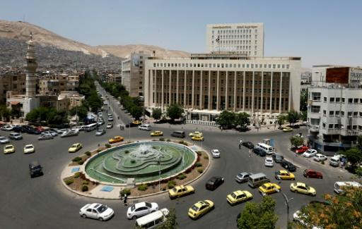Vehicles drive along the roundabout past the Central Bank of Syria in the capital Damascus