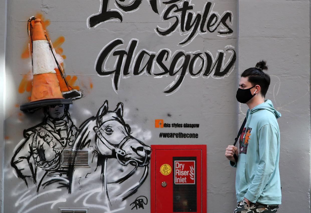 A member of the public wearing a face mask walks passed art work on a wall in Glasgow. (Photo by Andrew Milligan/PA Images via Getty Images)