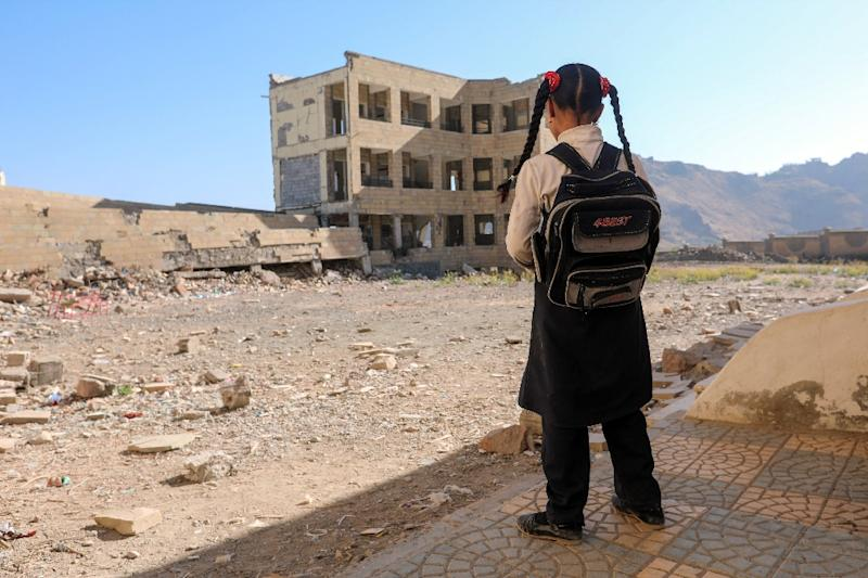 A Yemeni school girl stands outside a school, that was damage in an air strike in the southern Yemeni city of Taez in March 2017 (AFP Photo/Ahmad AL-BASHA)