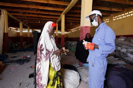 A woman receives payment for delivering plastic litter to be recycled into roofing tiles at the Envirogreen recycling plant in Mogadishu, Somalia January 13, 2019. Picture taken January 13, 2019. REUTERS/Feisal Omar