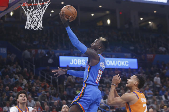 Oklahoma City Thunder guard Dennis Schroeder (17) shoots in front of Phoenix Suns forward Elie Okobo, right, during the first half of an NBA basketball game Friday, Dec. 20, 2019, in Oklahoma City. (AP Photo/Sue Ogrocki)