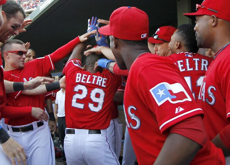Texas Rangers' Adrian Beltre (29) is congratulated in the dugout after his solo home run that came off a pitch from Los Angeles Angels relief pitcher Ernesto Frieri (49) in the eighth inning of a baseball game, Sunday, Sept. 29, 2013, in Arlington, Texas. The Rangers won 6-2. (AP Photo/Tony Gutierrez)