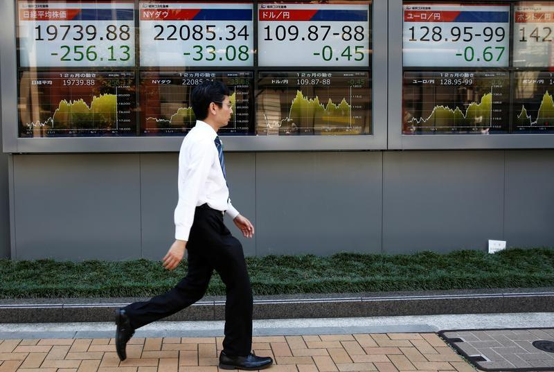A man walks past electronic boards showing Japan's Nikkei average, the Dow Jones Industrial Average and foreign exchange rates outside a brokerage at a business district in Tokyo