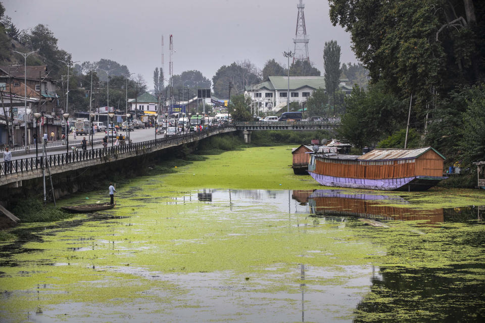 A Kashmiri boatman rows his boat through the polluted water of Dal Lake in Srinagar, Indian controlled Kashmir, Thursday, Sept. 9, 2021. Weeds, silt and untreated sewage are increasingly choking the sprawling scenic lake, which dominates the city and draws tens of thousands of tourists each year. (AP Photo/Mukhtar Khan)