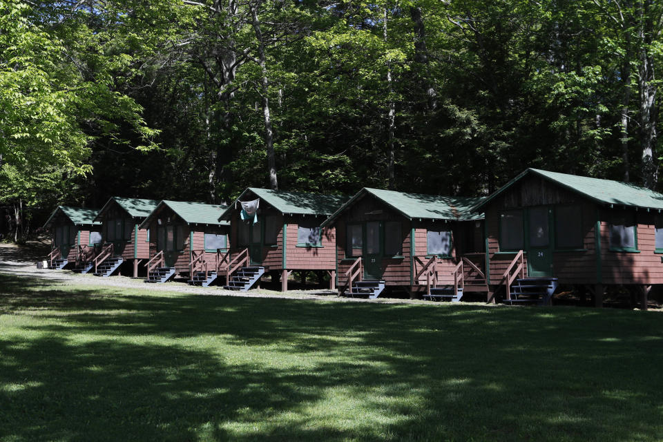 FILE - This Thursday, June 4, 2020 file photo shows a row of cabins at a summer camp in Fayette, Maine. On Friday, May 28, 2021, the Centers for Disease Control and Prevention posted guidance saying kids at summer camps can skip wearing masks outdoors, with some exceptions. Children who aren't fully vaccinated should still wear masks outside when they're in crowds or in sustained close contact with others – and when they are inside, and fully vaccinated kids need not wear masks indoors or outside, the CDC says. (AP Photo/Robert F. Bukaty, File)