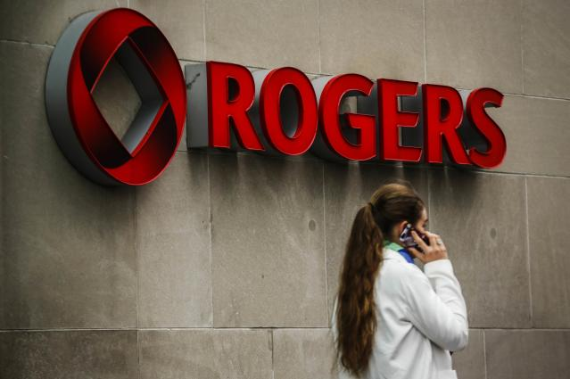 A woman speaks on her cell phone in front of a Rogers Communications Inc sign before the company's annual general meeting for shareholders in Toronto April 22, 2014. (Reuters)