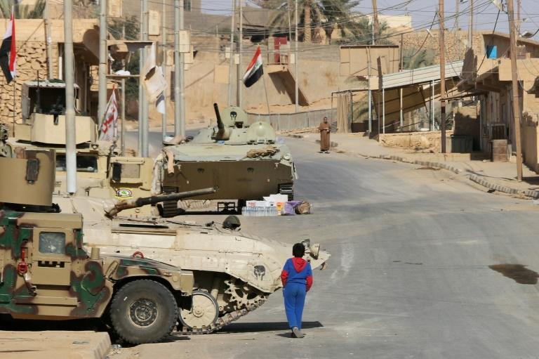 A boy walks past Iraqi forces vehicles in Rawa on November 18, 2017, after troops retook the Euphrates valley town from Islamic State group jihadists