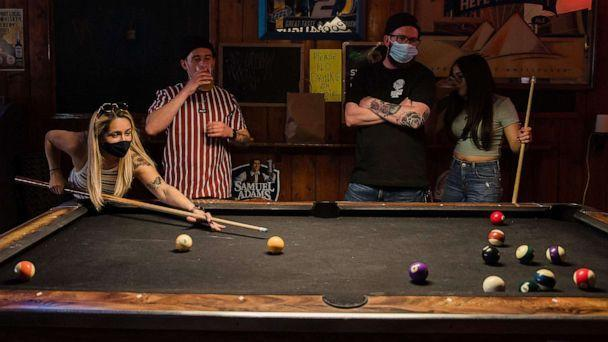 PHOTO: People wearing face masks play pool at Cheswick's West bar in Ocean Beach in San Diego, Feb. 13, 2021. (Ariana Drehsler/AFP via Getty Images, FILE)