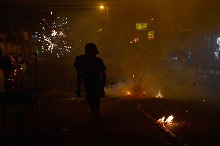 A reveller sets off firecrackers as residents usher New Year in Manila on January 1, 2013