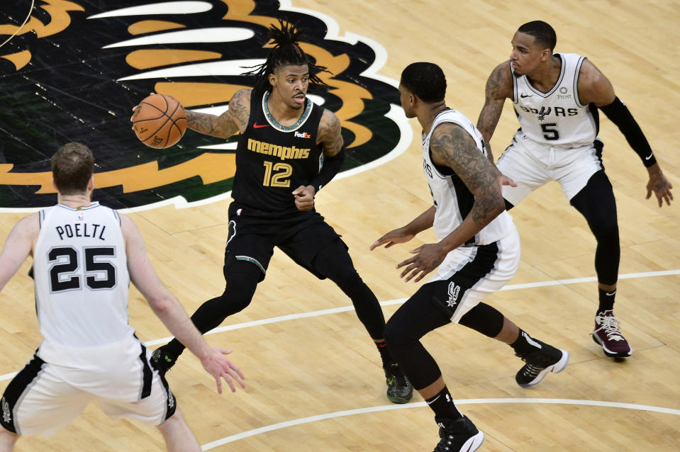 Memphis Grizzlies guard Ja Morant (12) is defended by San Antonio Spurs center Jakob Poeltl (25), forward Rudy Gay and guard Dejounte Murray (5) during the second half of an NBA basketball Western Conference play-in game Wednesday, May 19, 2021, in Memphis, Tenn. (AP Photo/Brandon Dill)