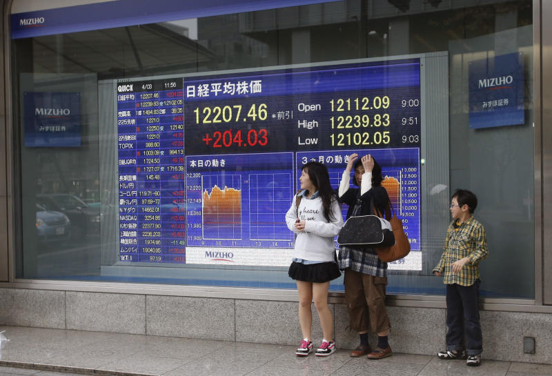 A family shelters from the rain in front of an electronic stock indicator in Tokyo Wednesday, April 3, 2013. Asian stock markets mostly rose Wednesday, boosted by more evidence the U.S. economic recovery is gaining traction. Japan's Nikkei 225 index in Tokyo jumped 1.7 percent to 12,207.46 as a fall in the yen enticed investors back into export shares. (AP Photo/Shizuo Kambayashi)