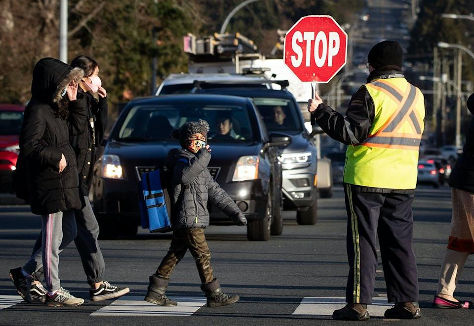"<span class=""caption"">A crossing guard stops traffic as students arrive at École Woodward Hill Elementary School, in Surrey, B.C., Feb. 23, 2021. </span> <span class=""attribution""><span class=""source"">THE CANADIAN PRESS/Darryl Dyck</span></span>"