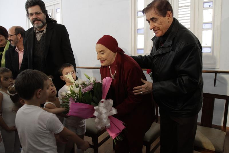Cuba's Prima Ballerina Alicia Alonso, center, receives flowers from ballet students at the headquarters of Cuba's National Ballet after receiving the 2010 National Award of Education in Arts in Havana, Cuba, Monday, Dec. 27, 2010. Third left is Abel Prieto, Cuba's Minister of Culture and at right is Fernando Alonso, Alicia Alonso's husband. (AP Photo/Franklin Reyes)