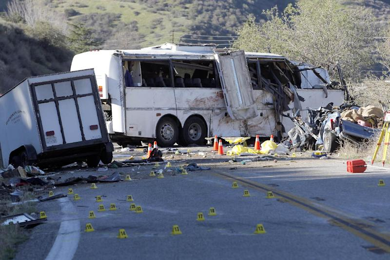 """FILE - In this Feb. 4, 2013, file photo, evidence markers dot the road in front of the wreckage of a tour bus that crashed on Feb. 3, in the Southern California mountains near San Bernardino. Federal accident investigators called on Nov. 7, 2013, for a probe of the government agency charged with ensuring the safety of commercial vehicles, saying their own look into four tour bus, including the one on Feb. 3, and truck crashes that killed 25 people raises """"serious questions"""" about how well the agency is doing its job. Federal inspectors gave the California tour bus company safety clearance a month before the accident. Seven passengers and a pickup truck driver were killed, 11 passengers were seriously injured and 22 others received minor to moderate injuries. The bus driver told passengers the bus' brakes had failed. (AP Photo/Nick Ut, File)"""