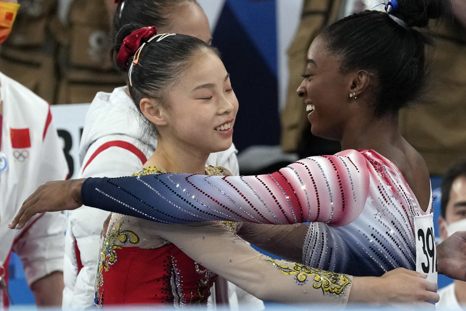 Gold medalist Guan Chenchen, of China, left, gets a hug from bronze medalist Simone Biles, of the United States, after performing on the balance beam during the artistic gymnastics women's apparatus final at the 2020 Summer Olympics, Tuesday, Aug. 3, 2021, in Tokyo, Japan. (AP Photo/Gregory Bull)