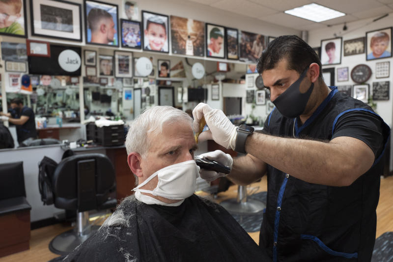 Howard Kaplan gets a haircut from Eli Gilkarov at Jack's Barbershop, Tuesday, June 9, 2020, in Larchmont, N.Y. Counties north of New York City are reopening businesses as part of Phase 2 during the coronavirus pandemic. The barbershop is doing haircuts by appointment with limited numbers of customers in the store at any time. (AP Photo/Mark Lennihan)