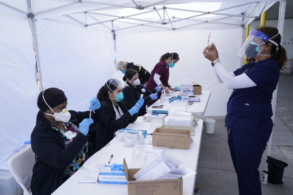 FILE - In this March 3, 2021, file photo, public health nurse Dyah Moore, right, and other health care workers prepare Moderna COVID-19 vaccines for farmworkers at a County of Santa Clara mobile vaccination clinic at Monterey Mushrooms, an agricultural employer under the United Farm Workers union contract, amid the coronavirus pandemic in Morgan Hill, Calif. In some California counties, vaccination drives are targeting farmworkers. (AP Photo/Jeff Chiu, File)