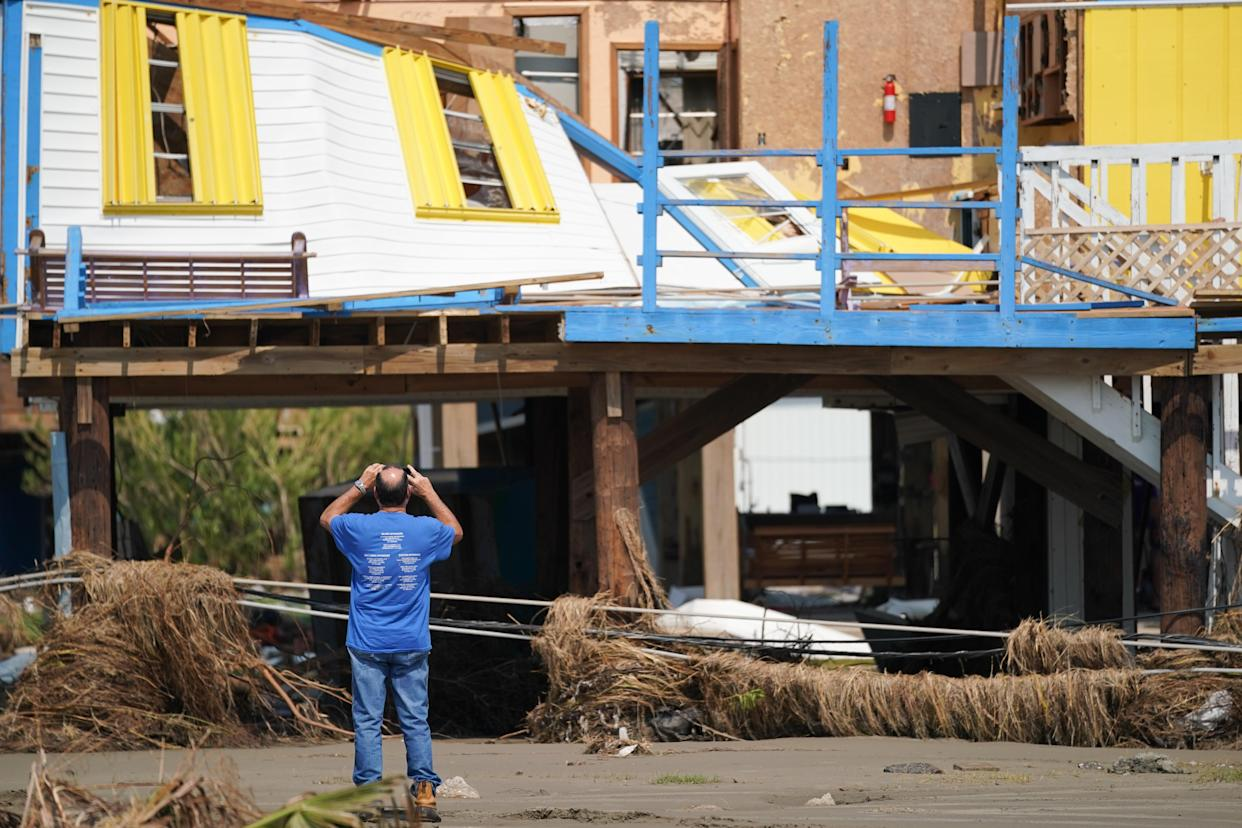 A man documents storm damage to a house after Hurricane Ida