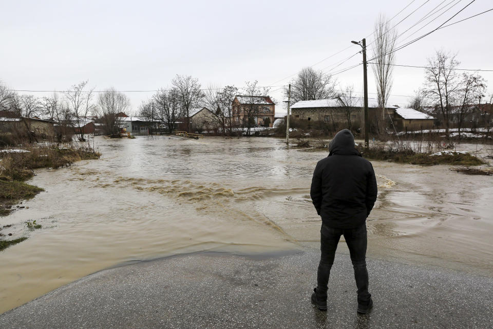 A villager is stranded on the road leading to the village of Preoc, which was flooded following heavy rain and snowfall, Kosovo on Monday, Jan. 11, 2021. Many roads have been blocked and bridges damaged, according to the authorities. There have been no casualties or lost livestock so far. (AP Photo/Visar Kryeziu)