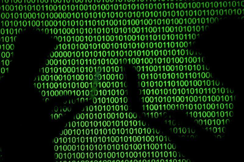 FILE PHOTO: Silhouettes of laptop users are seen next to a screen projection of binary code are seen in this picture illustration
