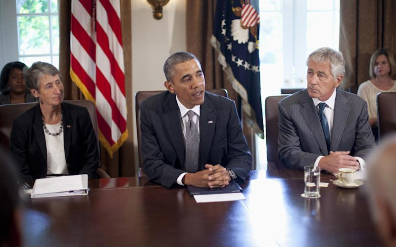 President Barack Obama, flanked by Interior Secretary Sally Jewell, left, and Defense Secretary Chuck Hagel, speaks to members of the media before the start of a cabinet meeting, Thursday, Sept. 12, 2013, in the Cabinet Room of the White House in Washington. (AP Photo/Pablo Martinez Monsivais)