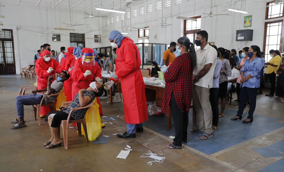 Sri Lankan health officials take swab samples from employees of the Colombo municipal council to test for COVID-19 in Colombo, Sri Lanka, Wednesday, Oct. 7, 2020. Authorities in Sri Lanka on Wednesday widened a curfew and warned of legal action against those evading treatment for COVID-19 after reporting an escalating cluster centered around a garment factory in the capital's suburbs. (AP Photo/Eranga Jayawardena)