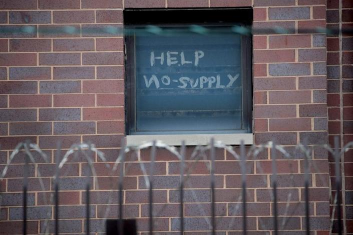 A sign pleading for help hangs in a window at the Cook County jail complex on April 09, 2020 in Chicago, Illinois. (Photo by Scott Olson/Getty Images)