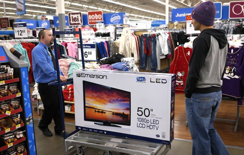 """A Walmart employee helps a customer with a 50"""" TV on sale for $218 on Black Friday in Broomfield"""