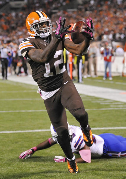 Cleveland Browns wide receiver Josh Gordon (12) grabs a 37-yard touchdown pass against Buffalo Bills free safety Aaron Williams in the third quarter of an NFL football game Thursday, Oct. 3, 2013, in Cleveland. (AP Photo/David Richard)