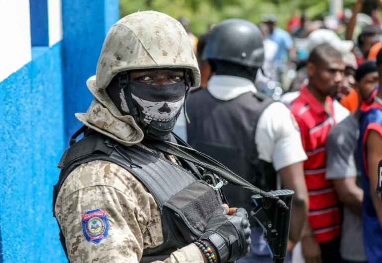 Police look on as a crowd surrounds the Petionville Police station where armed men accused of being involved in the assassination of President Jovenel Moise are being held