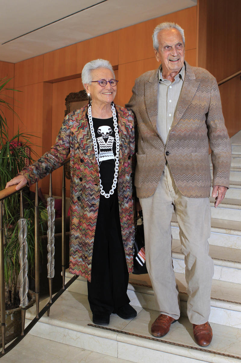 In this photo taken on March 22, 2012 Italian fashion designer Ottavio Missoni is flanked by his wife Rosita Jelimini in Milan, Italy. Italian fashion company Missoni says its co-founder, Ottavio Missoni, has died in his home earlier on Thursday, May 9, 2013 in northern Italy. Missoni, who was 92, founded the iconic fashion brand of zigzagged-patterned knitwear along with his wife, Rosita, in 1953. The Missonis are a family fashion dynasty, with the couple's children and their offspring involved in expanding the brand. (AP Photo/Luca Bruno)