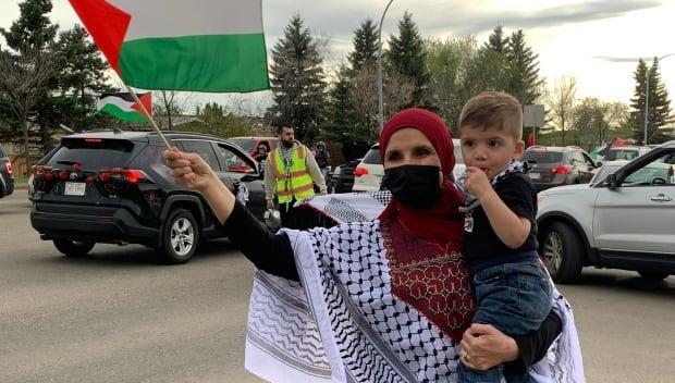 A woman waves a Palestinian flag during a car convoy organized by pro-Palestinian demonstrators in Edmonton on Saturday.