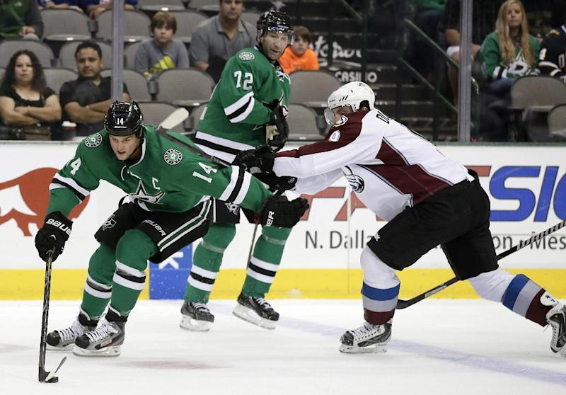 Dallas Stars left wing Jamie Benn (14) attempts to gain control of the puck under pressure of Colorado Avalanche center Matt Duchene (9) as Stars' Erik Cole (72) watches in the first period of an NHL hockey preseason game on Thursday, Sept. 26, 2013, in Dallas. (AP Photo/Tony Gutierrez)