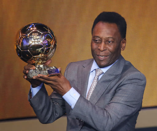 Brazil's soccer legend Pele displays the honorary prize he received at the FIFA Ballon d'Or 2013 Gala in Zurich, Switzerland, Monday, Jan. 13, 2014. (AP Photo/Michael Probst)