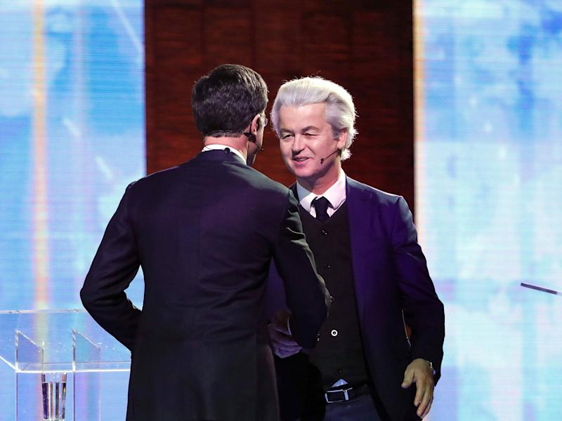 Netherlands' far-right politician Geert Wilders (R) of the PVV party and Netherlands' prime minister Mark Rutte of the VVD Liberal party shake hands before debating on 13 March, 2017: Getty