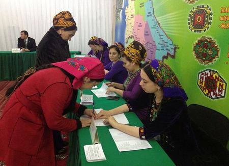 A woman signs to collect her ballot during a presidential election at a polling station in Ashgabat Turkmenistan